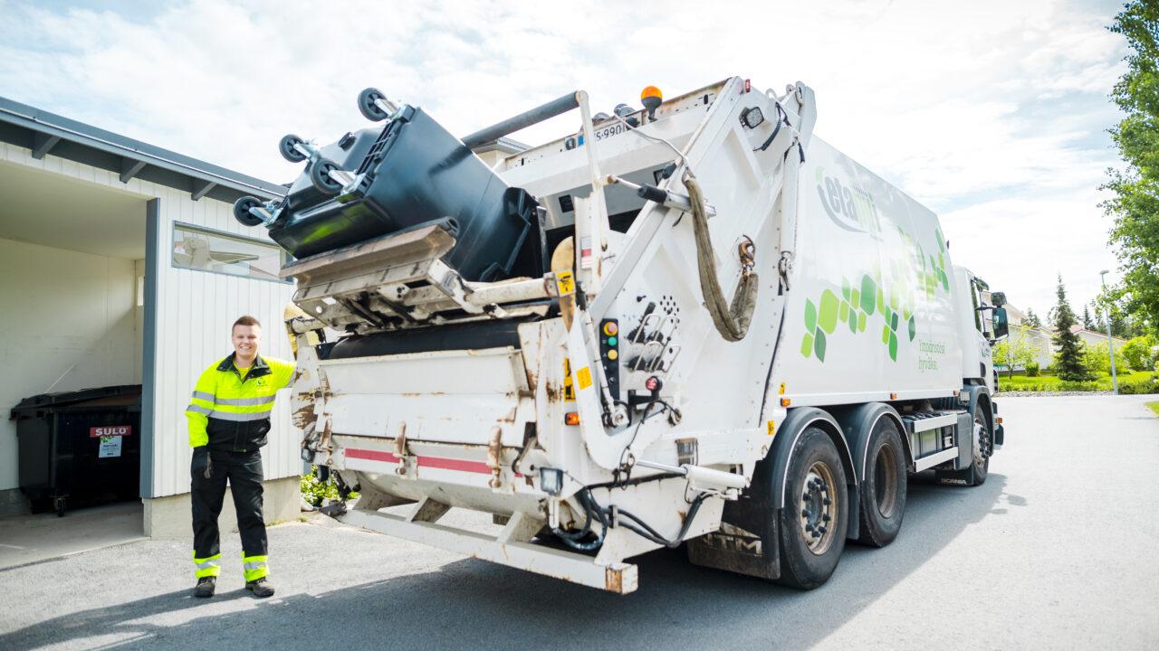 Jätteenkuljettaja tyhjää jäteastiaa jäteautoon.
