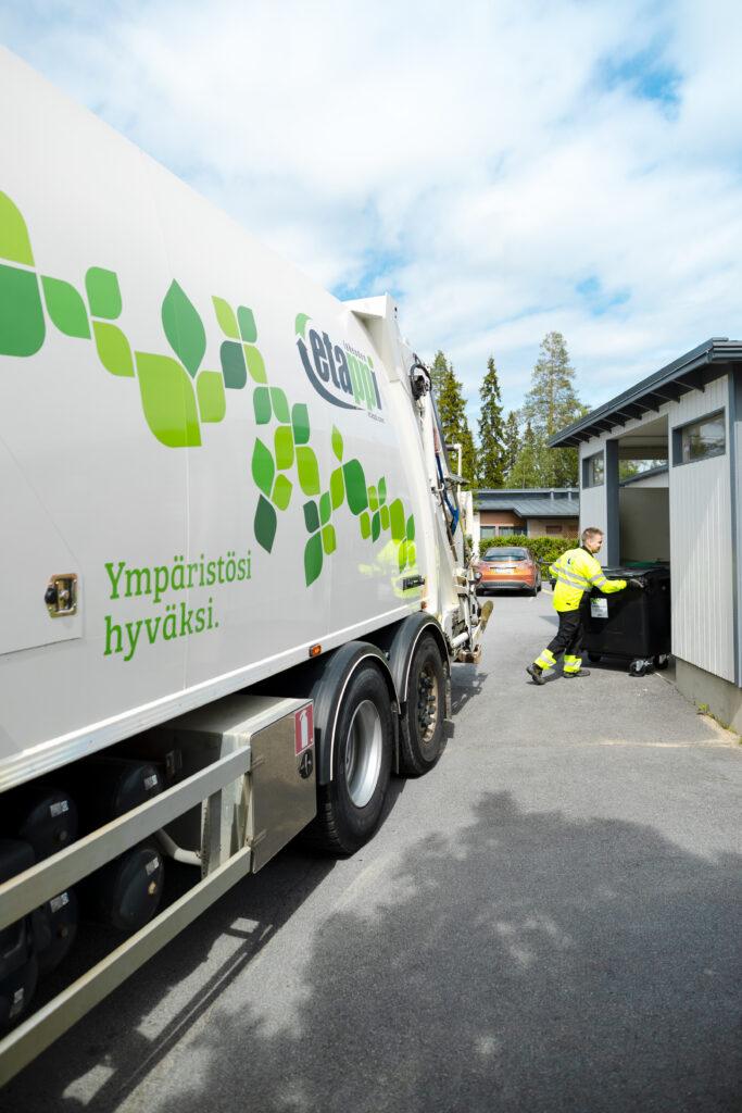 Jätteenkuljettaja palauttaa tyhjennettyä jäteastiaa autolta takaisin taloyhtiön jätehuoltoon.