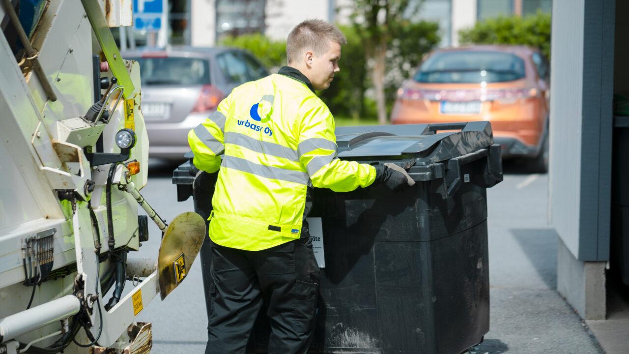 Jätteenkuljettaja jäteastian kanssa.