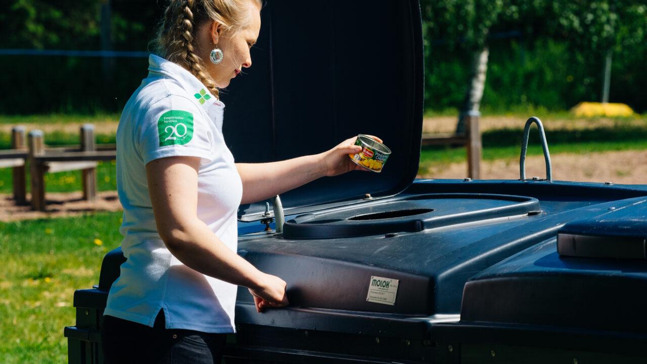 Nainen laittaa metallijätettä jäteastiaan.