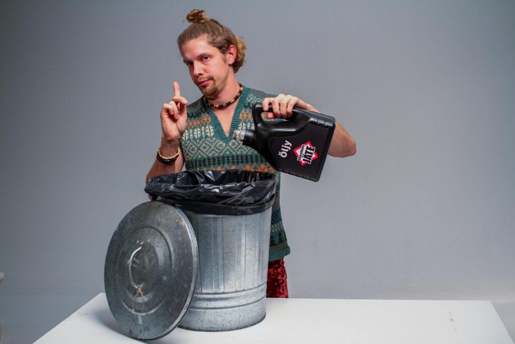 Mies kaatamassa öljyä roskaämpäriin. Toinen sormi on pystyssä kiellon merkiksi.